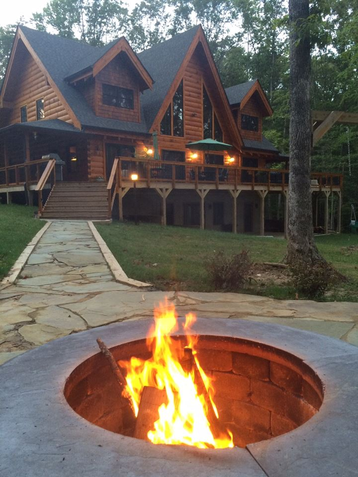 A campfire in front of a cabin