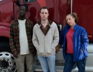 A middle aged man, woman, and a younger man stand in front of an 18-wheeler looking directly into the camera.